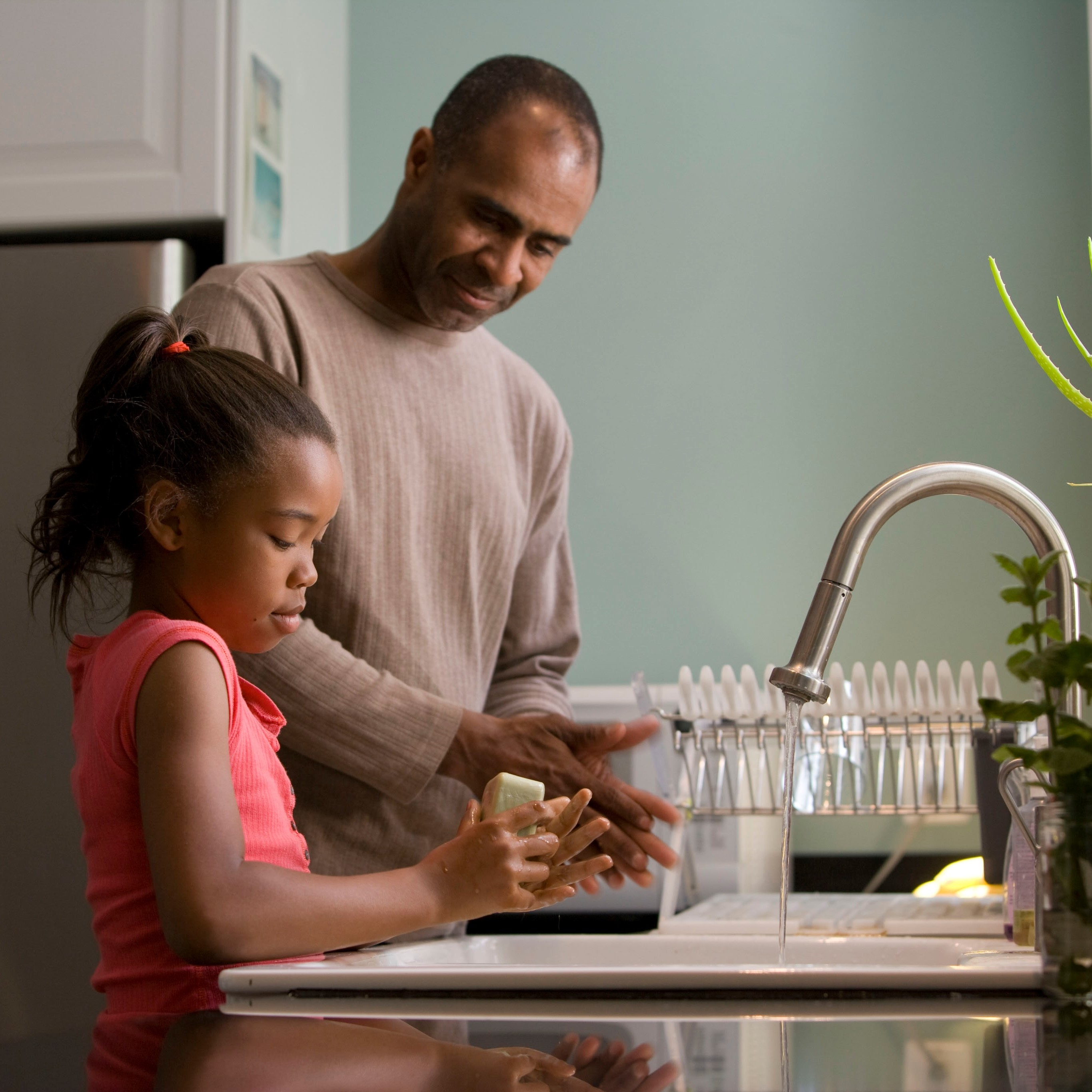 Father and daughter washing hands in kitchen