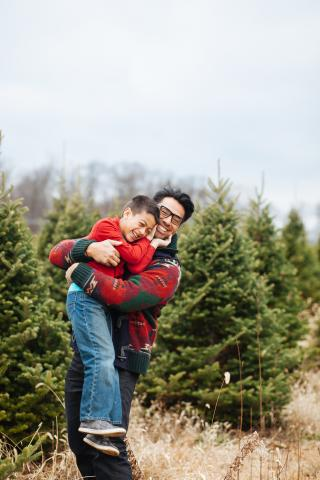 Father and son having fun at a Christmas tree farm